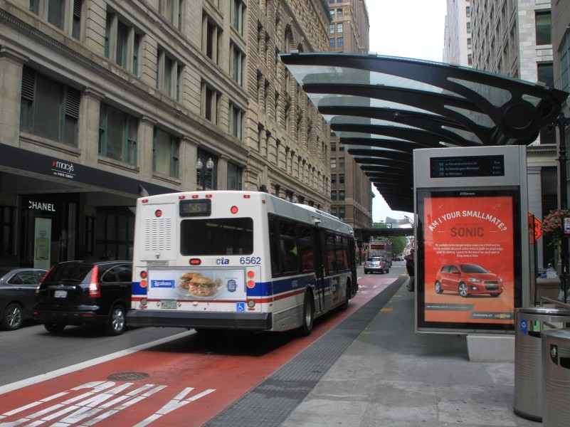 A CTA bus passes through a protected bus shelter in a downtown environment.