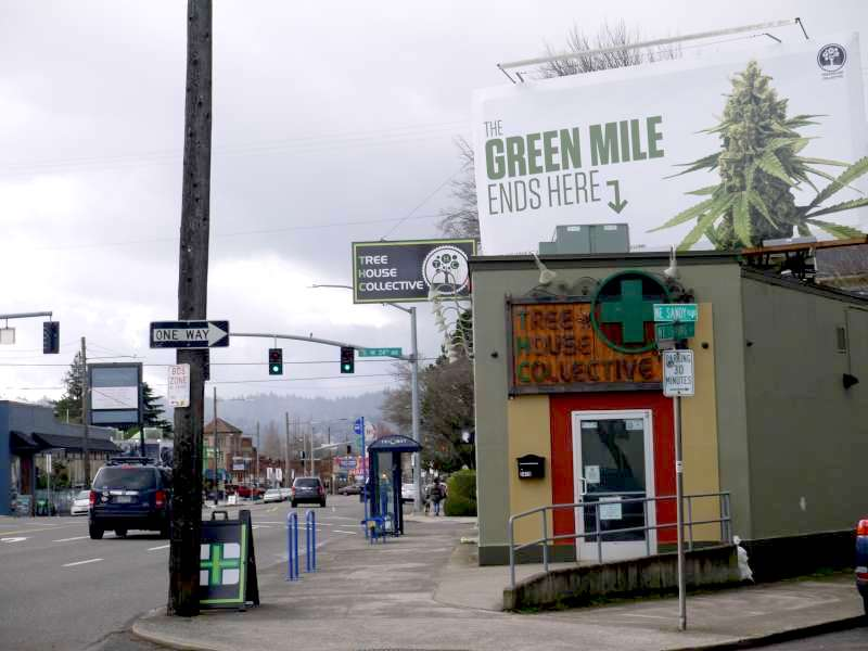 """A cannabis retail store sits on a busy street corner in Portland, Oregon. They are openly advertising cannabis sales on a billboard above their store with a picture of a cannabis flower and the words """"The Green Mile ends here"""" with an arrow pointing to the store. There are cars driving by on the street and a pedestrian is seen walking in the distance."""