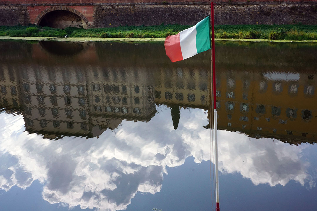 The focal point of this picture is the Italian flag, waving in front of the Arno. The city''s waterfront is completely reflecting on the River Arno's surface.