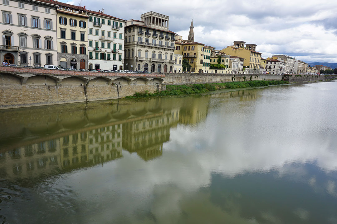 Taken from the Ponte Grazie bridge, originally the Rubaconte, this image depicts the waterfront streets of Florence, reflecting in the Arno river with clouds above.