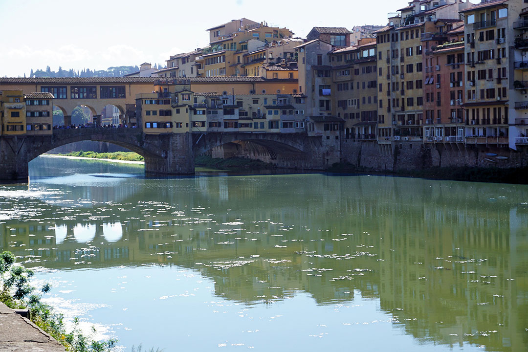 A view of the River Arno in Florence, with the Ponte Vecchio Bridge in the Foreground. Contrasting, bright colors of the structures reflect through the water