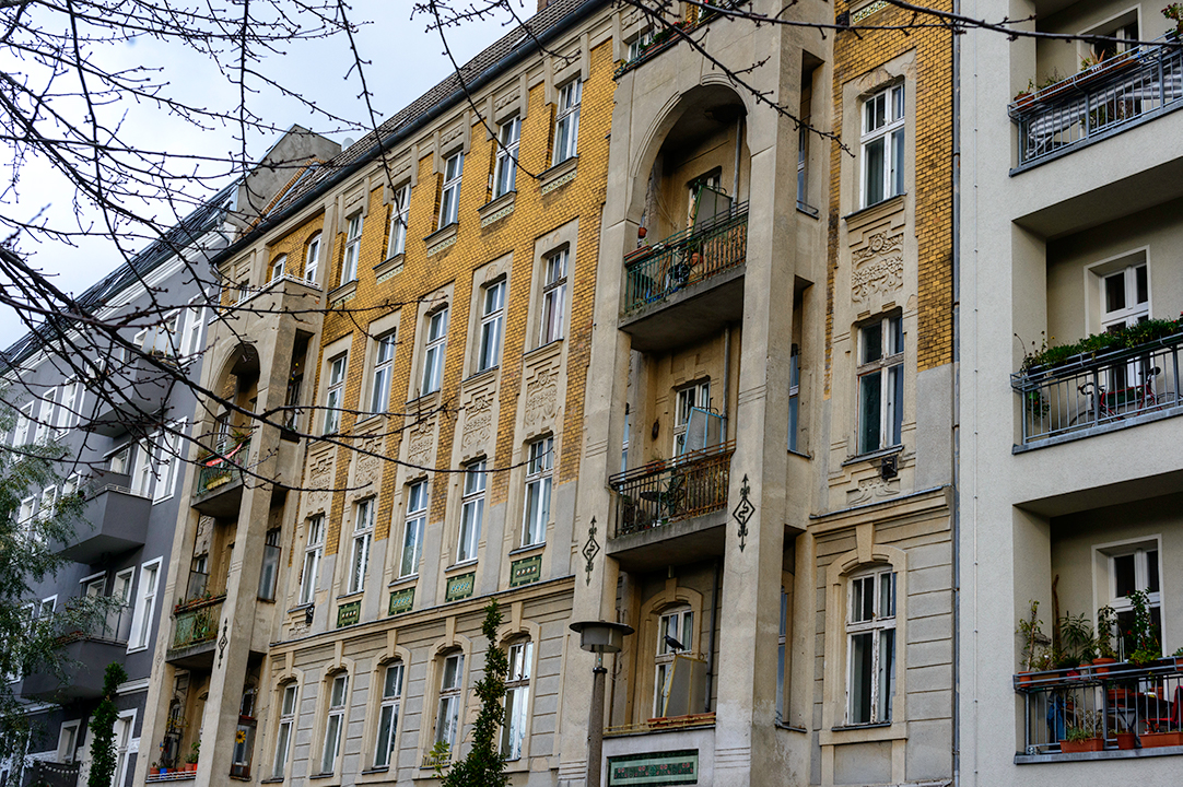 Old residential building next to newly renovated apartment buildings in Prenzlauer Berg, Berlin, Germany