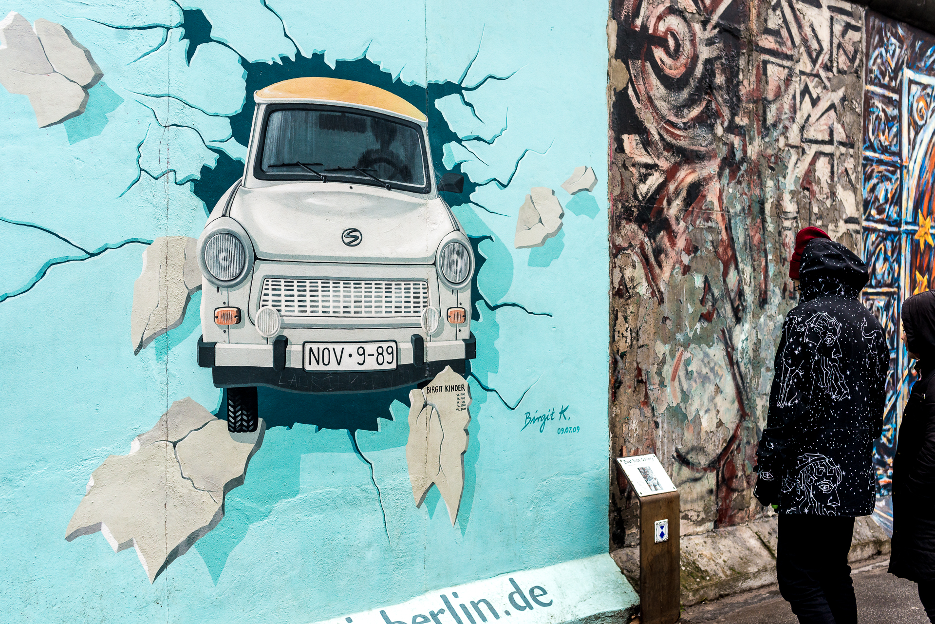 A man reading about the East Side Gallery memorial in front of La Trabant, a painting on the East Side Gallery of a East German car breaking through the wall in Berlin Germany