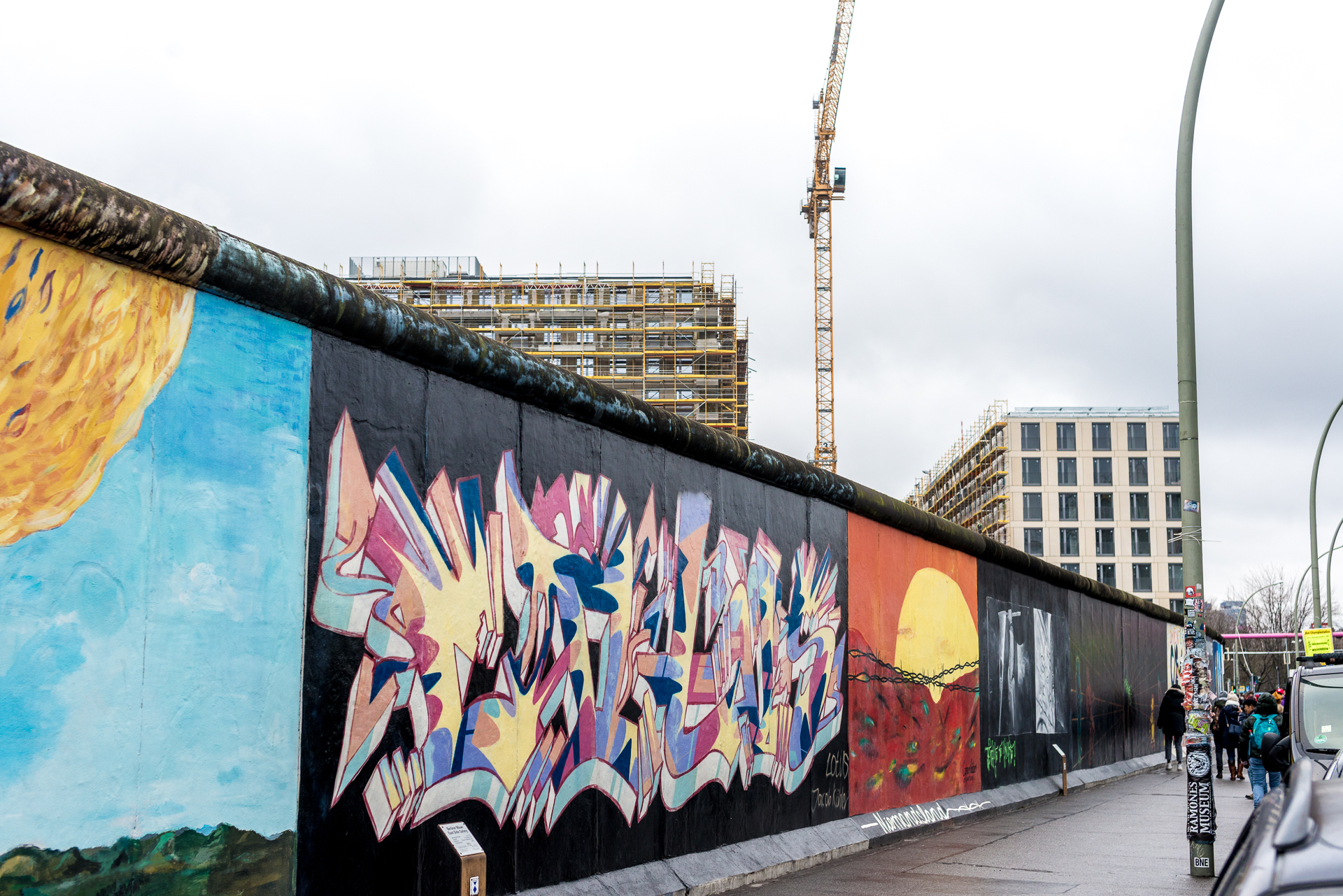 A stretch of the East Side Gallery showing different bright- colored murals on the wall in Berlin, Germany