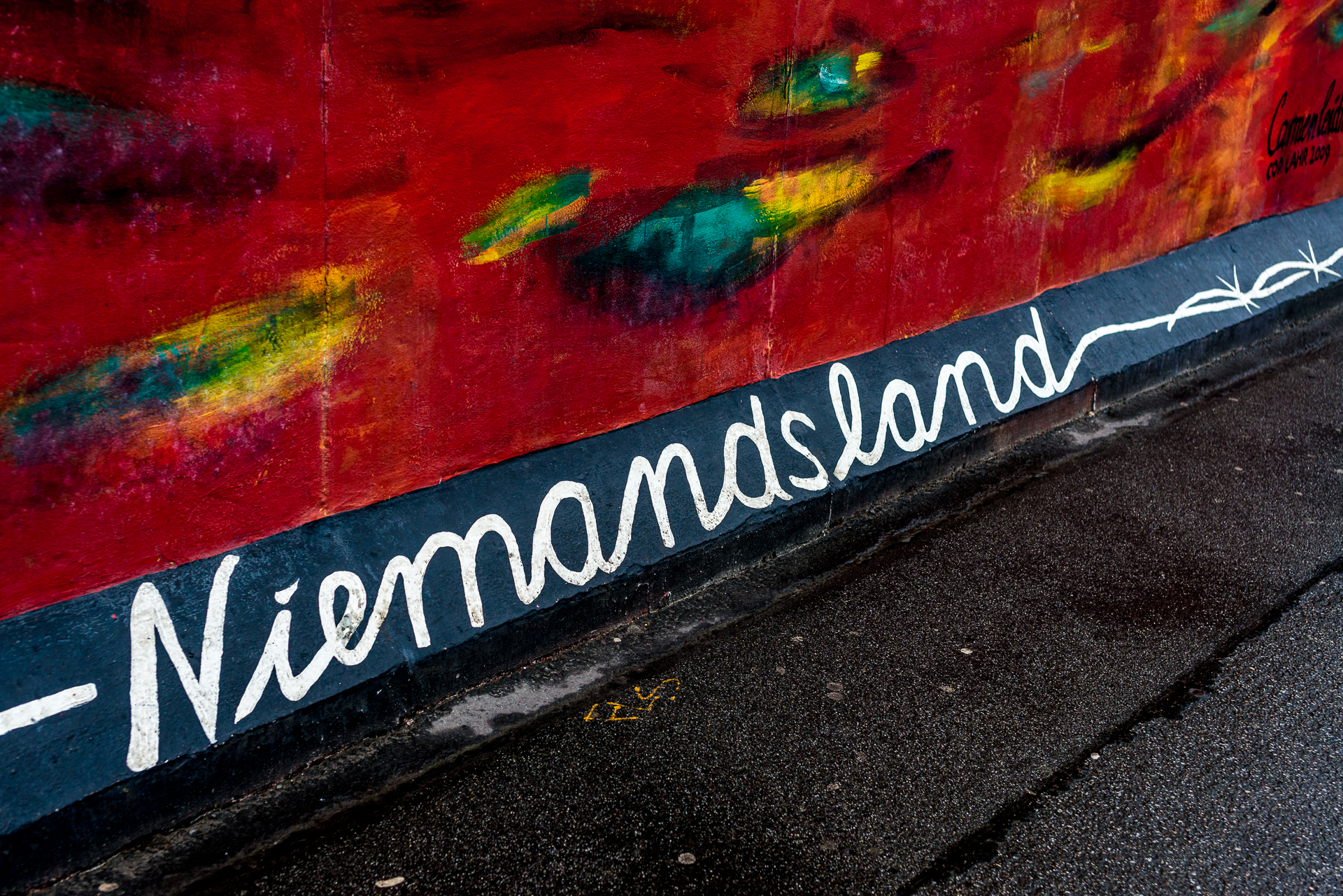 """German word """"Niemandsland"""" painted in white on black background on the East Side Gallery in Berlin, Germany. It translates to """"No mans land"""" in English."""