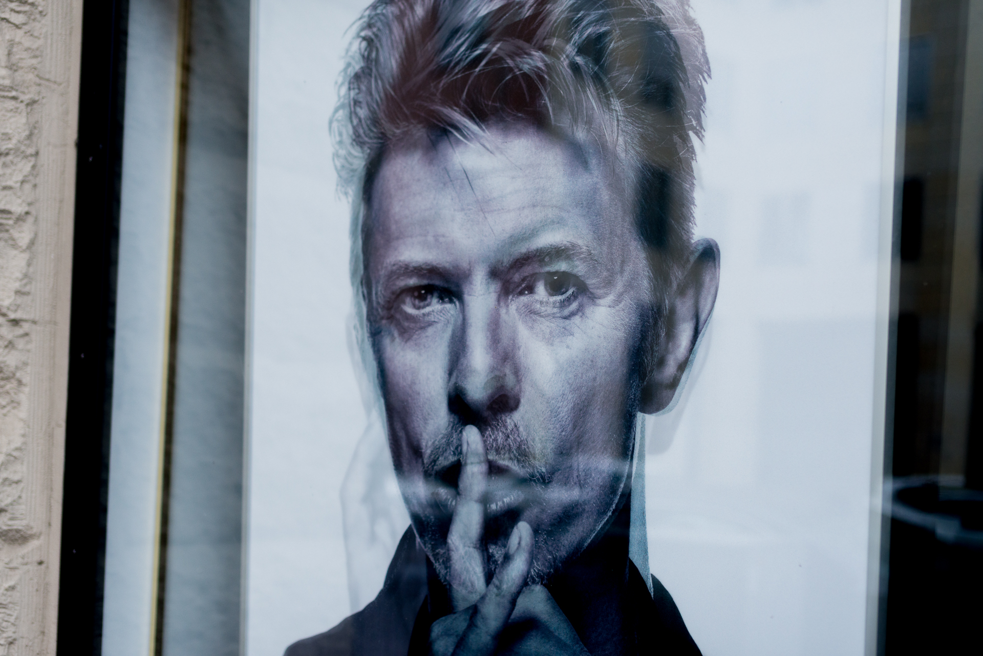 Black and white portrait of David Bowie that is hung behind glass in front of Hansa Studios in Berlin, Germany