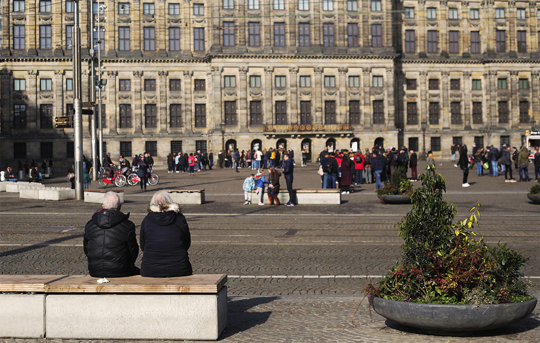 Two visitors of Dam Square share a bench that is intended to secure the space from potentially hostile vehicles.