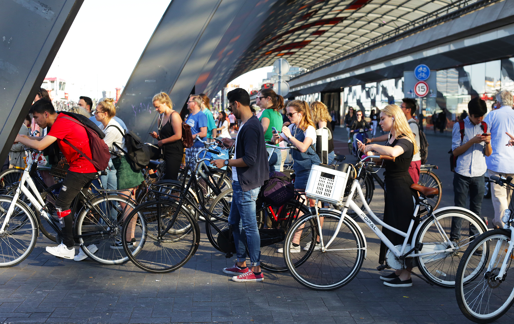 A crowd of people wait patiently with their bikes at the Buiksloterweg Ferry Terminal next to Central Station