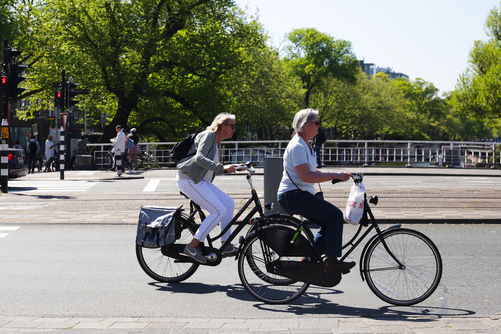 Two women share a calm bike ride through De Pijp neighborhood in Amsterdam