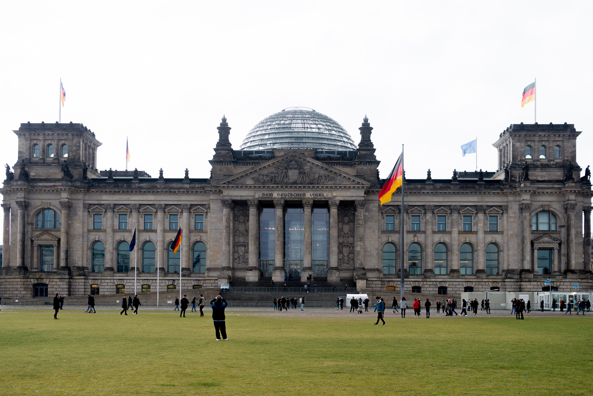 Tourists swarming the green lawns in front of the German Bundestag in Berlin, Germany