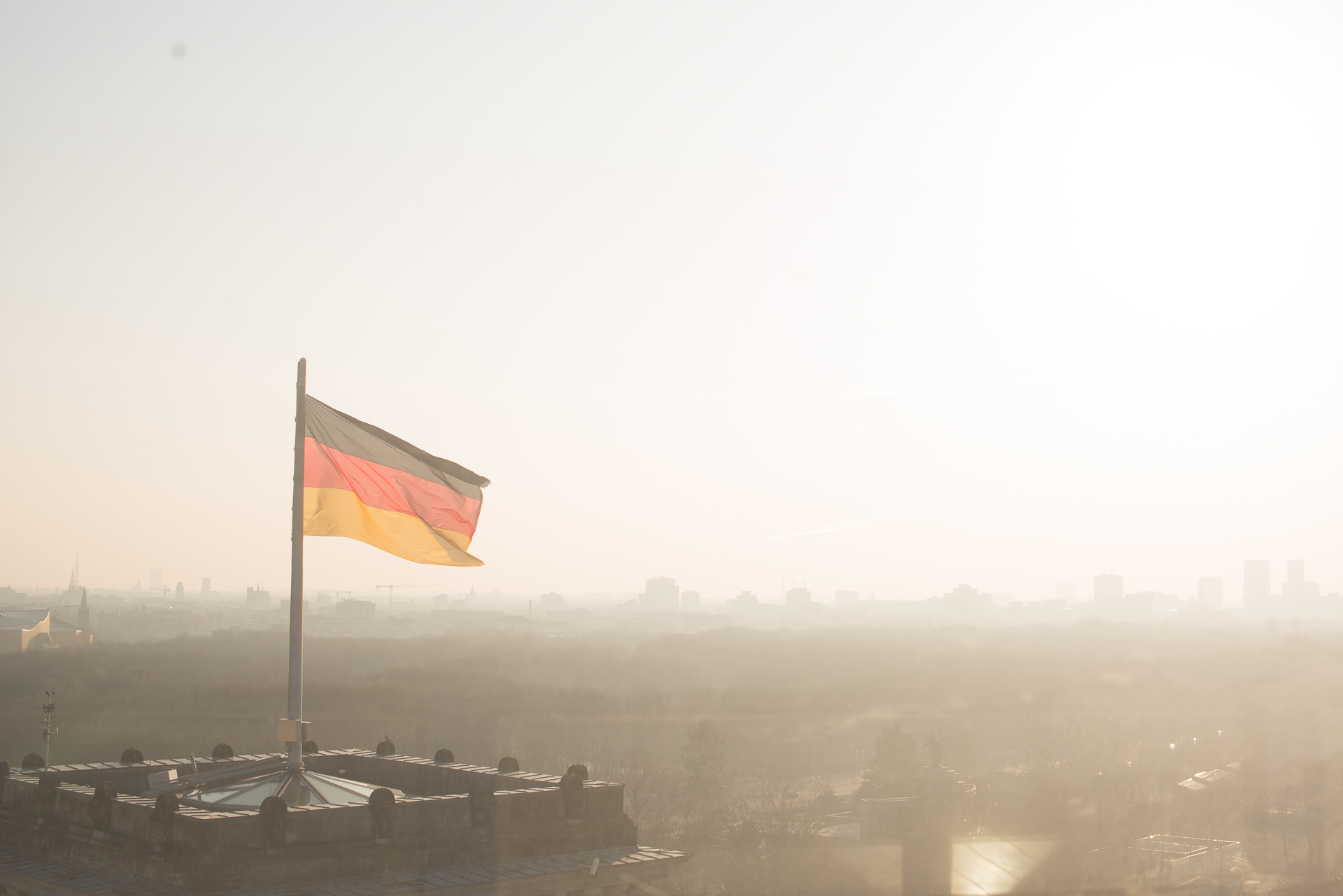 View on top of the German Reichstag showing Berlin's skyline and a single German flag flying